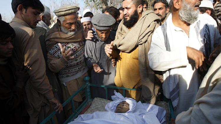 Pakistani villagers look at the body of health worker Hilal Khan, who was killed by gunmen, in Wahidgari, on the outskirts of Peshawar, Pakistan on Thursday, Dec. 20, 2012. Another victim from attacks on U.N.-backed anti-polio teams in Pakistan died on Thursday, bringing the three-day death toll in the wave of assaults on volunteers vaccinating children across the country to nine, officials said. (AP Photo/Mohammad Sajjad)