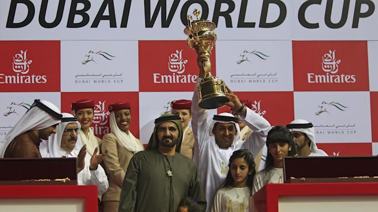 FILE - A Saturday, March 31, 2012 photo from files showing Sheikh Mohammed bin Rashid Al Maktoum, prime minister and ruler of Dubai, on his left, Mahmoud Al Zarooni, the trainer of Monterosso from Great Britain holds the trophy after they won the Dubai World Cup race in Dubai, United Arab Emirates. The doping scandal that led to the downfall of Godolphin trainer Mahmood al-Zarooni is now helping fuel a call for an outright ban on anabolic steroids in horse racing.  (AP Photo/Kamran Jebreili, File)