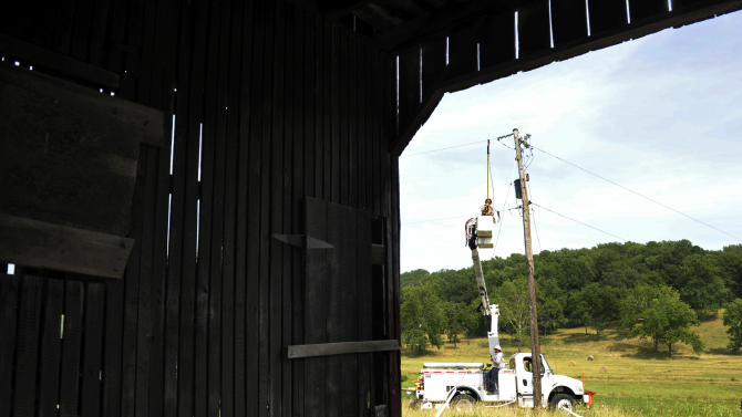 A Gulf Power lineman works to restore a power line near a barn in Middleburg, Va., Tuesday, July 3, 2012. Severe storms swept through the area leaving many homes and businesses without electricity. (AP Photo/Cliff Owen)