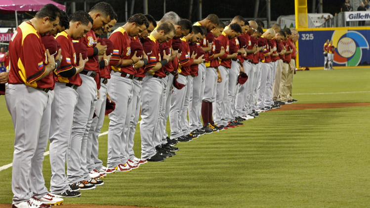 Players and coaches of team Venezuela observe a minute of silence to pay tribute to late Venezuela's President Hugo Chavez before the start of the World Baseball Classic first round game against the Dominican Republic in San Juan, Puerto Rico, Thursday, March 7, 2013. (AP Photo/Andres Leighton)