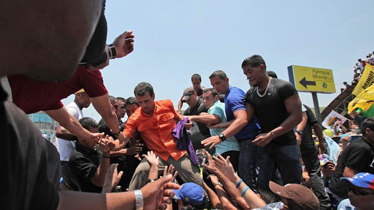 Opposition presidential candidate Henrique Capriles is helped onto to a stage upon his arrival to a campaign rally in San Fernando de Apure, Venezuela, Thursday, April 11, 2013. Capriles is running against the ruling party candidate Nicolas Maduro in the upcoming April 14 presidential election. (AP Photo/Fernando Llano)