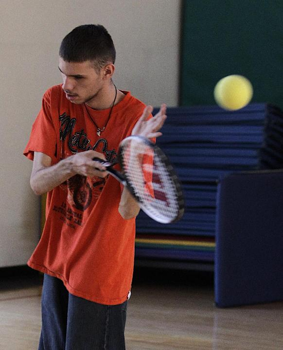 In this photo taken Oct. 16, 2012, Austin Benavidez, who is blind, practices his tennis serve using an oversized ball filled with ball bearings at the California School for the Blind in Fremont, Calif