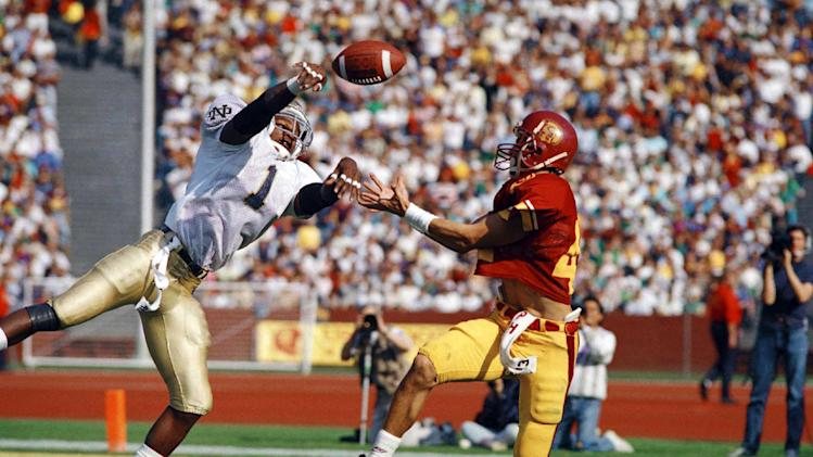 FILE - In this Nov. 26, 1988, file photo, Notre Dame cornerback Todd Lyght (1) breaks up a pass intended for Southern California's Erik Affholter, right, during the first quarter of their NCAA college football game in Los Angeles. A 65-yard touchdown run by Notre Dame's Tony Rice, two touchdowns scored on short runs by tailback Mark Green and four turnovers for Southern California helped Notre Dame to a 27-10 win. The Associated Press takes a look at some of the memorable games in college football's greatest intersectional rivalry in anticipation of Southern California hosting No. 1 Notre Dame on Saturday, Nov. 24, 2012. (AP Photo/Reed Saxon, File)