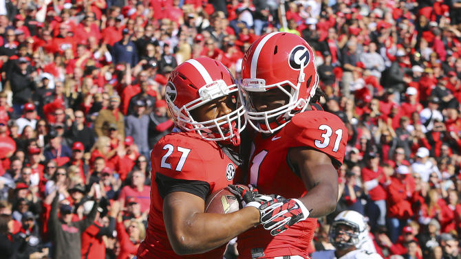 Georgia tailback Nick Chubb, left, celebrates his touchdown run with Chris Conley during the first quarter of an NCAA college football game against Charleston Southern, Saturday, Nov. 22, 2014, in Athens, Ga. (AP Photo/Atlanta Journal-Constitution, Curtis Compton)