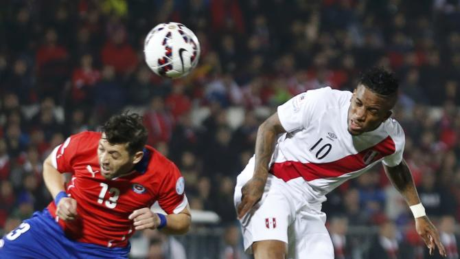Peru's Farfan heads the ball next to Chile's Rojas during their Copa America 2015 semi-final soccer match at the National Stadium in Santiago