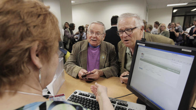 CORRECTS LAST NAME TO BOVA INSTEAD OF BORA - FILE - In this June 1, 2011, file photo, Jim Darby, 79, left, and his partner Patrick Bova, 73, apply for a civil union license at the Cook County Office of Vital Records in Chicago. Attorneys representing them and 24 other same-sex couples in a lawsuit challenging the state gay marriage ban asked a judge Wednesday, July 10, 2013, to rule quickly in their favor. (AP Photo/M. Spencer Green, File)
