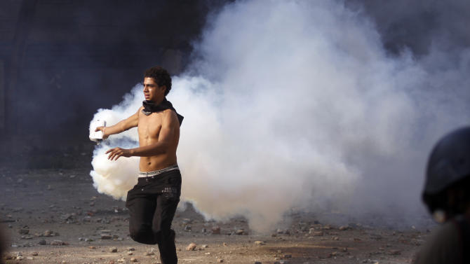 An Egyptian protester throws a gas canister away during clashes near the U.S. embassy in Cairo, Egypt, Thursday, Sept. 13, 2012. Protesters clashed with police near the U.S. Embassy in Cairo for the third day in a row. Egypt's Islamist President Mohammed Morsi vowed to protect foreign embassies in Cairo, where police were using tear gas to disperse protesters at the U.S. mission. (AP Photo/Khalil Hamra)