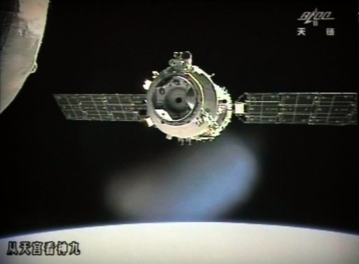 <p>This photo of the giant screen at the Jiuquan Space Centre shows the Shenzhou-9 spacecraft preparing to link with the Tiangong-1 module. A Chinese spacecraft on Sunday successfully completed the country's first manual docking in orbit, a milestone in an ambitious programme to build a space station by the end of the decade.</p>