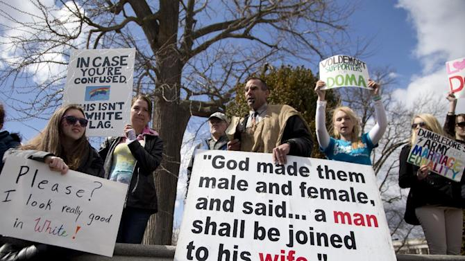 Allan Hoyle of North Carolina, with the large white sign, center, speaks out against gay marriage across from the street from the Supreme Court in Washington, Wednesday, March 27, 2013, after the court heard arguments on the Defense of Marriage Act (DOMA) case. The U.S. Supreme Court, in the second day of gay marriage cases, turned Wednesday to a constitutional challenge to the federal law that prevents legally married gay Americans from collecting federal benefits generally available to straight married couples. (AP Photo/Carolyn Kaster)