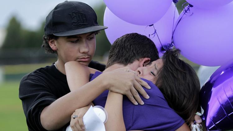 Students comfort each other Saturday, July 21, 2012, during a vigil at Gateway High School in Aurora, Colo., for AJ Boik, who was a student at the school and who was killed along with 11 others when a gunman opened fire in a movie theater. (AP Photo/Ted S. Warren)