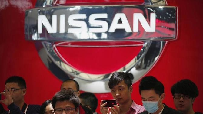 People take pictures of Nissan cars during the 15th Shanghai International Automobile Industry Exhibition in Shanghai