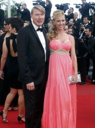 "Former Formula One driver Mika Hakkinen (L) poses with his wife Marketa Kromatova on the red carpet as she arrives for the screening of the film ""Behind the Candelabra"" in competition during the 66th Cannes Film Festival in Cannes May 21, 2013.                     REUTERS/Jean-Paul Pelissier (FRANCE  - Tags: ENTERTAINMENT SPORT)"