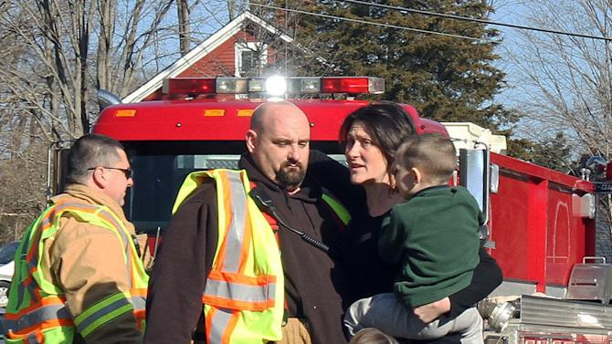 FILE - In this Dec. 14, 2012 file photo, a woman holding her children embraces a firefighter shortly after Adam Lanza opened fire, killing 26 people, including 20 children. While the people of Newtown do their best to cope with loss and preserve the memories of their loved ones, another class of residents is also finding it difficult to move on: the emergency responders who saw firsthand the terrible aftermath of last week's school shooting. (AP Photo/The Journal News, Frank Becerra Jr., File) NYC OUT, NO SALES, TV OUT, NEWSDAY OUT; MAGS OUT; MANDATORY CREDIT: THE JOURNAL NEWS, FRANK BECERRA JR.
