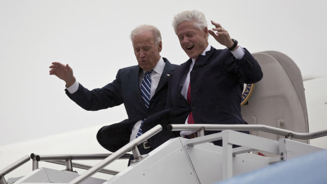 Vice President Joe Biden, left, accompanied by former President Bill Clinton walk carefully off Air Force Two during a rainstorm,, upon their arrival in Youngstown, Ohio, for a campaign stop, Monday, Oct. 29, 2012. (AP Photo/Matt Rourke)