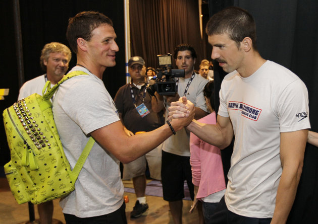 Ryan Lochte, left, and Michael Phelps greet each other as Lochte leaves and Michael Phelps arrives at a news conference at the U.S. Olympic swimming trials, Saturday, June 23, 2012, in Omaha, Neb. The trials starts on Monday. (AP Photo/Mark Humphrey)