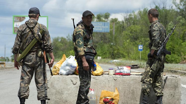 Pro-Russia separatists stand guard at a checkpoint outside the town of Metalist, north of Lugansk, eastern Ukraine, on June 28, 2014