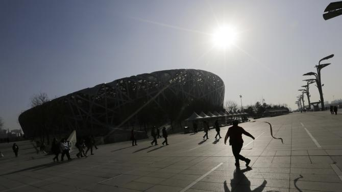 A resident dances near the National Stadium on a sunny winter day in Beijing