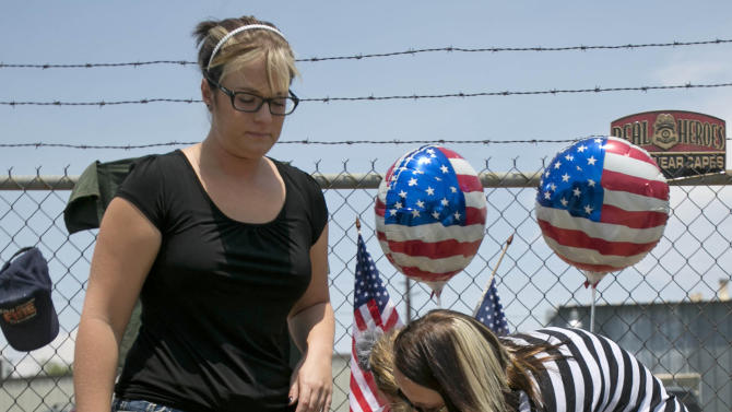 Angela Clark, left, her daughter Chloe, middle, and Theresa Winquest visit a makeshift memorial at the fire station Monday, July 1, 2013, in Prescott, Ariz., where an elite team of firefighters was based. Nineteen of the 20 members of the team were killed Sunday when a wildfire suddenly swept toward them in Yarnell, Ariz. (AP Photo/The Arizona Republic, Patrick Breen)
