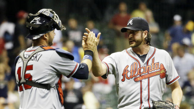 Atlanta Braves relief pitcher Jason Grilli and catcher A.J. Pierzynski celebrate after getting Milwaukee Brewers' Jonathan Lucroy to ground out and end the ninth inning of a baseball game Monday, July 6, 2015, in Milwaukee. The Braves won 5-3. (AP Photo/Morry Gash)