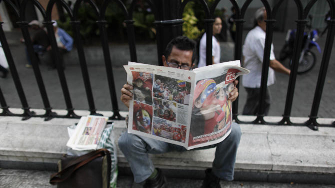 A man reads a local newspaper covered with pictures of supporters of Venezuela's President Hugo Chavez, in a plaza in Caracas, Venezuela, Tuesday, Feb. 19, 2013. Chavez is back in Venezuela after 10 weeks of cancer treatment in Cuba, but he remained silent and out of sight on Tuesday, closed away in a tightly guarded military hospital, leaving the nation to speculate about whether he can still govern, and for how long. (AP Photo/Ariana Cubillos)