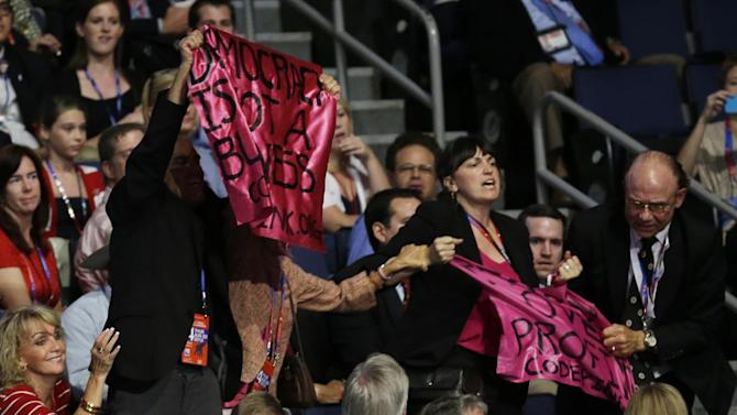 A protesters hold up banners during Republican presidential nominee Mitt Romney's speech during the Republican National Convention in Tampa, Fla., on Thursday, Aug. 30, 2012. (AP Photo/Charlie Neibergall)