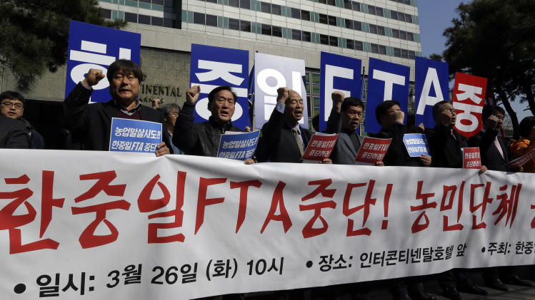 """South Korean farmers shout slogans against the Free Trade Agreement between South Korea, Japan, and China during a rally denouncing the FTA talks in front of the venue where the discussions are being held, in Seoul, South Korea, Tuesday, March 26, 2013.  Negotiations for a Free Trade Agreement between the three countries will be held from March 26 - 28. The writing reads """"Stop, FTA between South Korea, China and Japan."""" (AP Photo/Lee Jin-man)"""