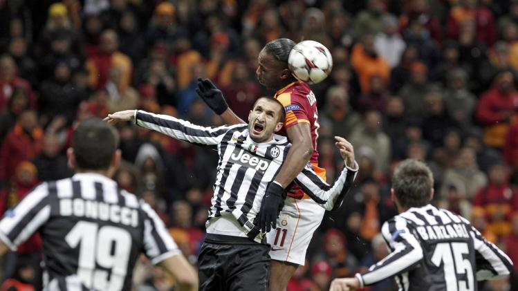 Drogba of Galatasaray and Chiellini of Juventus jump for a high ball during their Champions League soccer match in Istanbul