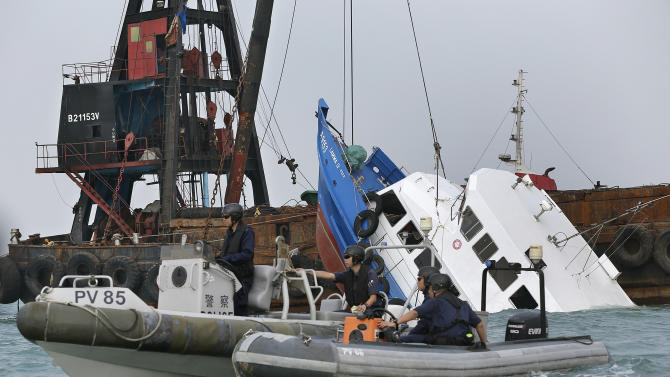 Police officers guard on a partially submerged boat after it collided with a ferry Monday night near Lamma Island, off the southwestern coast of Hong Kong Island Tuesday, Oct. 2, 2012. The boat packed with revelers on a long holiday weekend collided with a ferry and sank off Hong Kong, killing at least 36 people and injuring dozens, authorities said.  (AP Photo/Vincent Yu)
