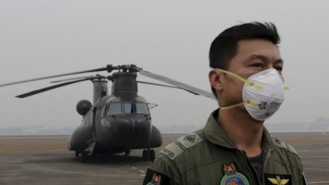 A member of RSAF wears a mask near a Chinook helicopter during preparation to fight forest fires, at an airport in Palembang, Indonesia