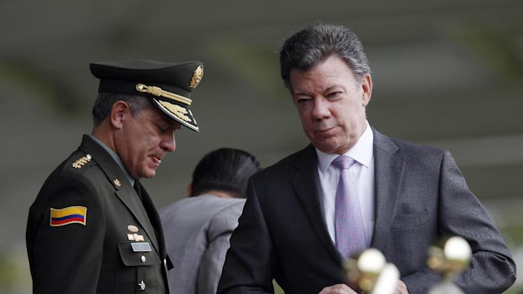 FILE - In this June 21, 2013 file photo, National Police Chief Gen. Jose Roberto Leon Riano stands next to Colombia's President Juan Manuel Santos, right, during a promotion ceremony for police in Bogota, Colombia. Santos promised decisive retaliation Sunday, July 21, 2013 after Colombia's main rebel band killed 19 soldiers in a single day in the biggest blow to the military since peace talks began in November. (AP Photo/Fernando Vergara, File)