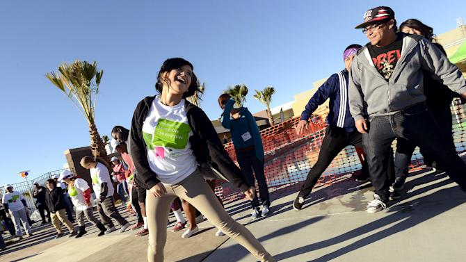 IMAGE DISTRIBUTED FOR HUMANA- A volunteer gets warmed up to build a one-of-kind, multi-generational playground at the Boys & Girls Clubs of Coachella Valley, on Saturday, Jan. 12, 2013, in Desert Hot Springs, Calif. Nearly 400 volunteers joined The Humana Foundation, the philanthropic arm of Humana, Inc., one of the nation's leading health care companies; KaBOOM!, a national non-profit organization that has built more 2,200 playgrounds; the Boys & Girls Clubs of Coachella Valley and the City of Desert Hot Springs to build the playground in just six hours. The playground build is one of many wellness-focused activities taking place leading up to the 2013 Humana Challenge PGA TOUR golf tournament, which will be held Jan. 14-20, 2013, in La Quinta, Calif. The build is a direct result of people who wore Humana pedometers and logged their steps during the 2012 Humana Challenge Walkit program, in which every step counted toward the donation made by the Humana Foundation (Gabriel Acosta / AP Images for Humana).
