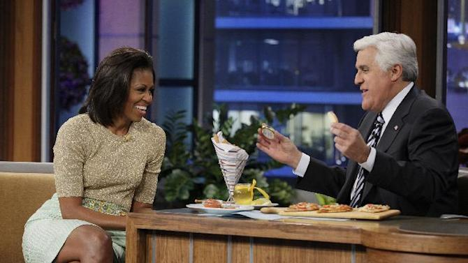 """FILE - In this Jan. 31, 2012 file image originally released by NBC shows first lady Michelle Obama speaking with host Jay Leno during an appearance on """"The Tonight Show with Jay Leno,""""  in Burbank, Calif.  NBC announced Monday, Aug. 6, that the first lady will make her third appearance on """"The Tonight Show"""" on Aug. 13 to talk about the London Olympics and life with President Barack Obama and their children at the White House. On her last stopover in January, the first lady promoted her """"Let's Move!"""" campaign to get kids excited about fitness and healthy eating habits. (AP Photo/NBC, Stacie McChesney, file)"""
