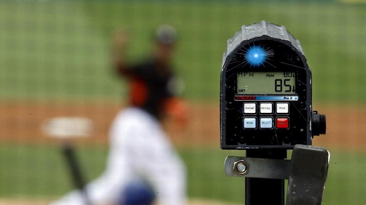 A radar gun registers 85 mph on a pitch by Miami Marlins' Henderson Alvarez, top, as he throws in the first inning of an exhibition spring training baseball game against the New York Mets, Monday, March 17, 2014, in Jupiter, Fla