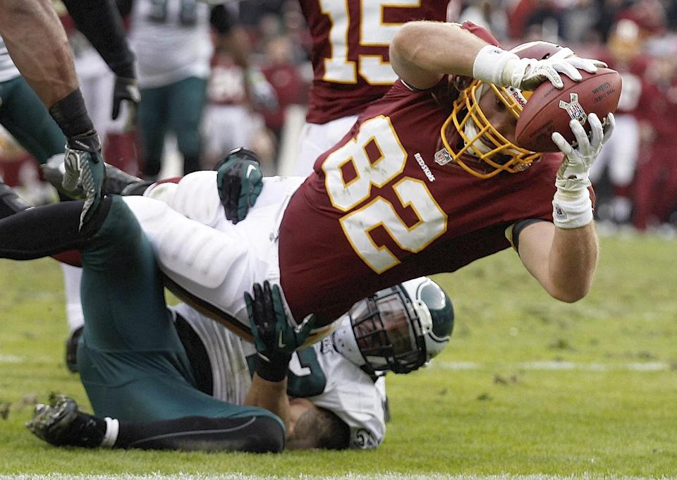 Washington Redskins tight end Logan Paulsen (82) drives into the end zone for a touchdown as Philadelphia Eagles free safety Kurt Coleman tries to hang on during the second half of an NFL football game in Landover, Md., Sunday, Nov. 18, 2012. (AP Photo/Alex Brandon)