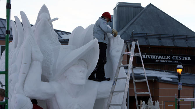 Team USA / Alaska captain, Pete Lucchetti sculpts at the top of his snow sculpture named 'Raven Myth' in the early morning out of a 12 foot tall, 20-ton block of compacted snow at the outdoor art gallery at the Riverwalk Center during the 23 annual International Snow Sculpture Championships in Breckenridge, Colo., on Saturday, Jan. 26, 2013. A total of 15 international teams participated in this invited competition. The sculptures will remain on display through Feb. 3, 2013, weather permitting. Visit www.gobreck.com for more information. (Nathan Bilow / AP Images for the Breckenridge Resort Chamber)