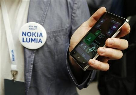 A worker poses with the new Nokia Lumia 925 at its launch in London