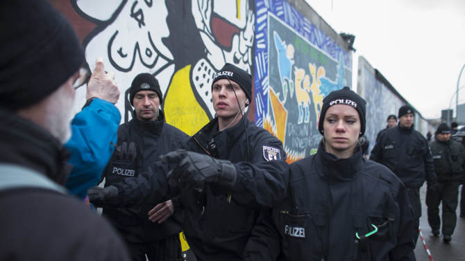 A German police officers reacts to protestors as they protect a part of the former Berlin Wall in Berlin, Germany, Friday, March 1, 2013. Construction crews stopped work Friday on removing a small section from one of the few remaining stretches of the Berlin Wall to make way for a condo project after hundreds of protesters blocked their path.(AP Photo/Markus Schreiber/Pool)