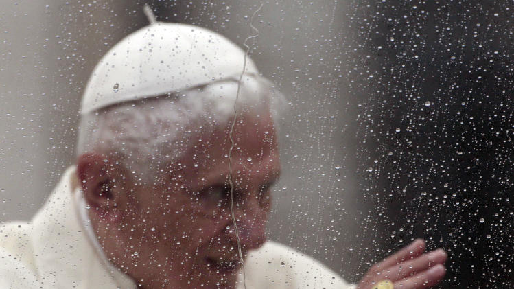 Pope Benedict XVI is seen behind a window covered in raindrops as he delivers his blessing from his pope-mobile in St. Peter's Square at the end of his general audience, at the Vatican, Wednesday, Oct. 31, 2012. (AP Photo/Gregorio Borgia)