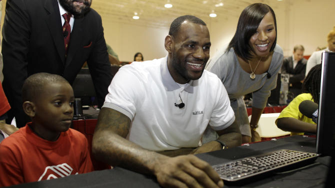 Miami Heat basketball player LeBron James, center, sits with Cam'ron Lightbourne, 8, left, and his girlfriend Savannah Brinson, right, at a new computer during a charity event at the Northwest Boys & Girls Club in Miami, Wednesday, March 2, 2011. The LeBron James Family Foundation partnered with HP to donate 1,000 computers nationwide to Boys & Girls Clubs of America. (AP Photo/Lynne Sladky)