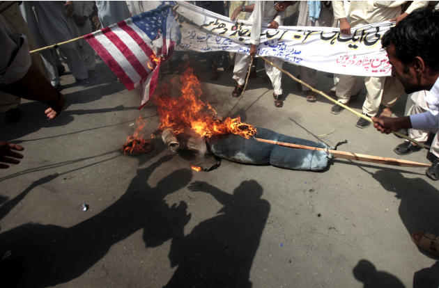 Pakistani protesters burn a representation of a U.S. flag and an effigy of President Barack Obama during a rally in Peshawar, Pakistan as a part of widespread anger across the Muslim world about a fil