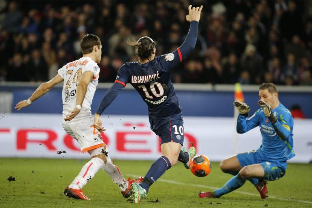 Paris Saint Germain's Zlatan Ibrahimovic fights for the ball with Valenciennes' Nicolas Penneteau and Gary Kagelmacher during their French Ligue 1 soccer match soccer match at Parc des Princes