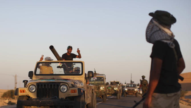 """Former rebel fighters celebrate as they pass by a checkpoint near Bani-Walid, Libya, Monday, Sept. 12, 2011. Three weeks after the fall of Tripoli appeared to herald the end of Libya's brutal war, the protracted battle over the loyalist bastions of Bani Walid and Sirte, Gadhafi's hometown, has dashed hopes of a speedy """"declaration of liberation"""" that would start the clock ticking on a transition to democracy. (AP Photo/Alexandre Meneghini)"""