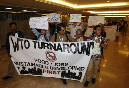 Protesters march through the meeting venue of the ninth WTO Ministerial Conference where concluding talks are taking place in Nusa Dua