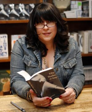 """Author E L James holds a copy of her new erotic fiction book """"Fifty Shades of Grey"""" at a book signing in Coral Gables, Fla., Sunday, April 29, 2012. (AP Photo/Jeffrey M. Boan)"""