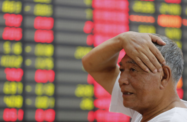 An investor gestures as he looks at the stock price monitor at a private securities company in Shanghai, China, Friday Aug. 10, 2012. Asian stock markets tumbled Friday as investors withdrew from riskier assets after China's trade suffered a steeper-than-expected slowdown. (AP Photo)