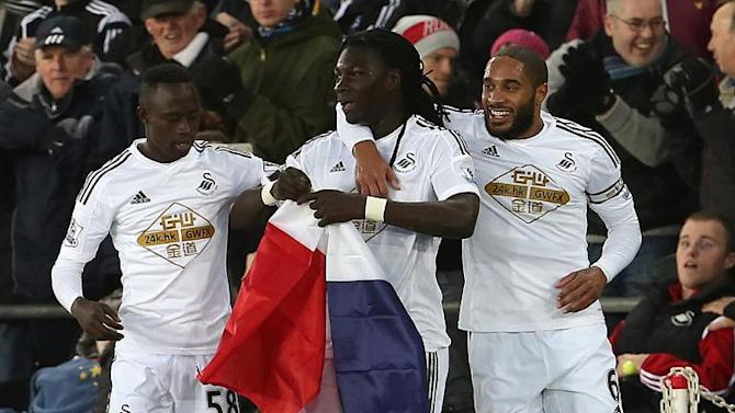 Swansea City's Bafetimbi Gomis (C) holds a French flag as he celebrates with Modou Barrow (L) and Ashley Williams during their English Premier League match against West Ham United at The Liberty Stadium on January 10, 2015