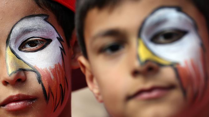 Two young Benfica supporters with their faces painted with an eagle, the team's mascot, pose for a photograph prior the Portuguese league soccer match between Benfica and Porto at Benfica's Luz stadium, Sunday, April 26, 2015, in Lisbon, Portugal. The match ended in a 0-0 draw and Benfica leads the competition ahead of second placed Porto. (AP Photo/Francisco Seco)