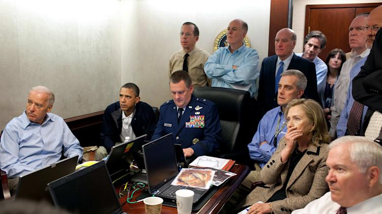 """FILE - In this May 1, 2011 image released by the White House and digitally altered by the source to obscure the details of a document on the table, President Barack Obama, second from left, Vice President Joe Biden, left, Secretary of Defense Robert Gates, right, Secretary of State Hillary Rodham Clinton, second right, and members of the national security team watch an update on the mission against Osama bin Laden in the Situation Room of the White House in Washington. A new book due out Tuesday, Oct. 16, 2012 says the president hoped to put Osama bin Laden on trial if he had surrendered during a U.S. raid. Author Mark Bowden quotes Obama as saying he thought he could make a strong political argument for giving bin Laden the full rights of a criminal defendant, to show U.S. justice applies even to him. In """"The Finish,"""" Bowden writes, however, that Obama said he expected the terror leader to go down fighting. (AP Photo/The White House, Pete Souza)"""