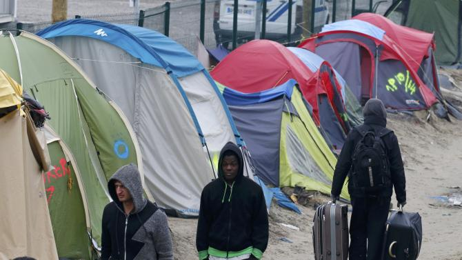 """Migrants with their belongings walk past tents at the start of their evacuation and transfer to reception centers in France, and the dismantlement of the camp called the """"Jungle"""" in Calais"""
