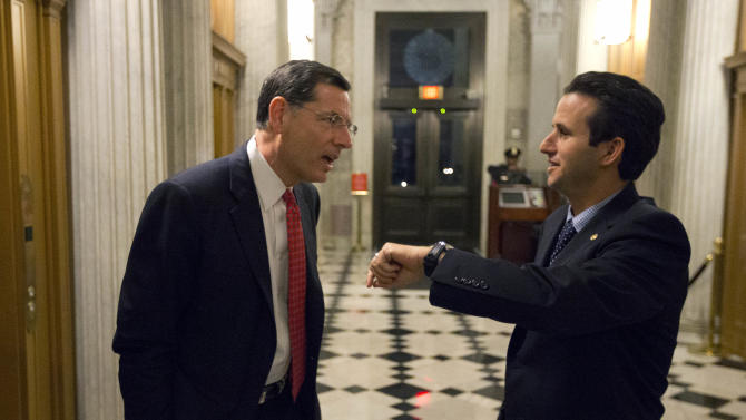 Sen. John Barrasso, left, R-Wyo., talks with Sen. Brian Schatz, D-Hawaii, who holds up his watch, near the Senate chambers after a vote on the fiscal cliff, on Capitol Hill Tuesday, Jan. 1, 2013 in Washington. The Senate passed legislation early New Year's Day to neutralize a fiscal cliff combination of across-the-board tax increases and spending cuts that kicked in at midnight. (AP Photo/Alex Brandon)